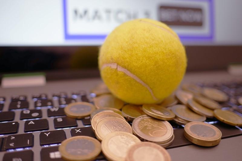 Tennis und Geldmünzen auf Laptop - Sportwetten