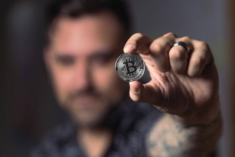 Mann hält Bitcoin in Kamera
