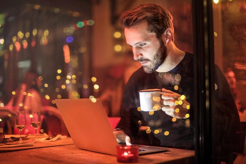 Mann sitzt am Laptop