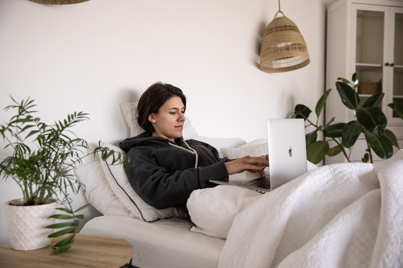 Frau mit Laptop im Bett macht kurze Pause