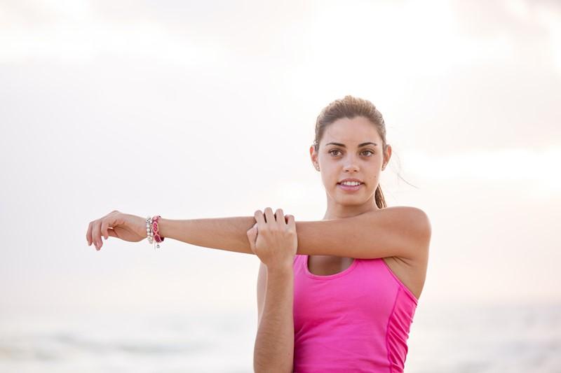 Eine Frau macht Sport und stretcht sich.