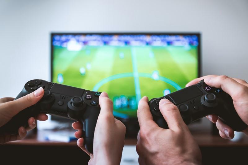 ZWei Personen spielen Fußball auf Spielekonsole