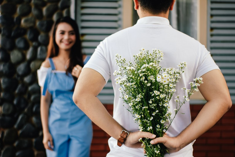 Ein Mann schenkt einer Frau Blumen