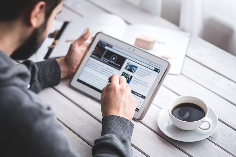 Ein Mann surft auf einem Tablet im Internet über einen Browser.