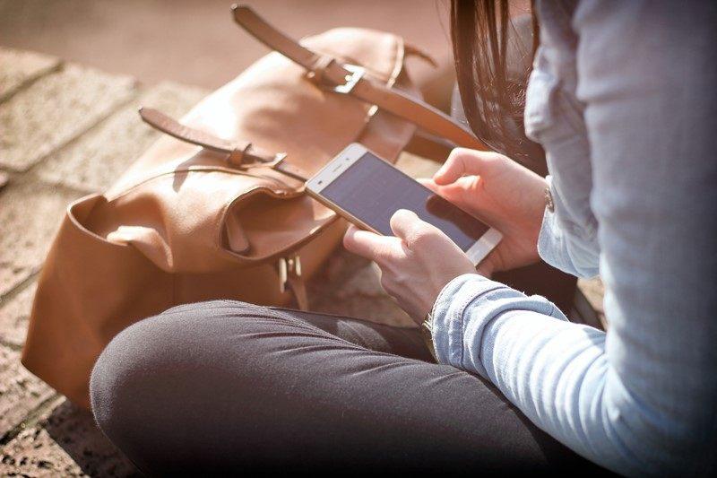 Eine Frau nutzt ihr Smartphone in der Freizeit zum Spielen.