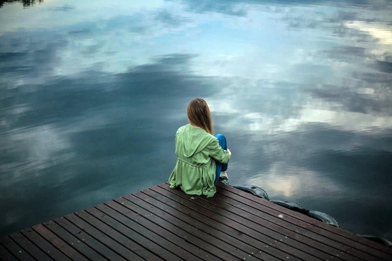 Frau sitzt allein auf Steg am Wasser