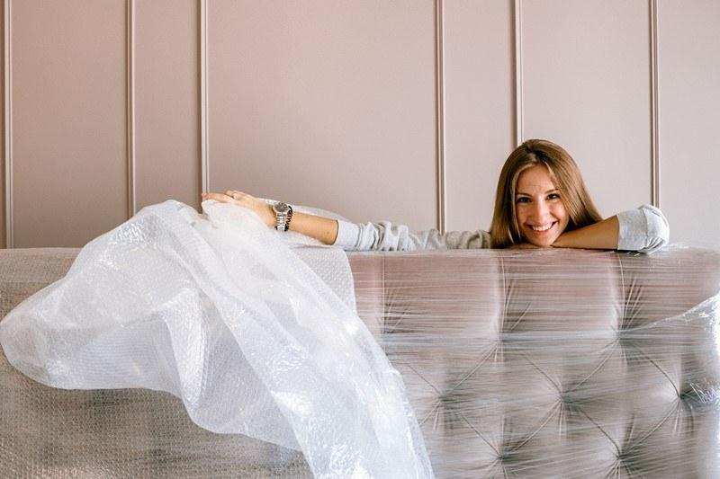 Eine Frau entpackt ihre Couch nach einem Umzug