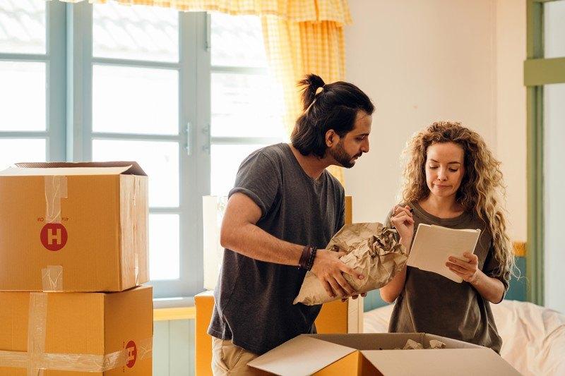 Paar packt Umzugskartons und macht sich Notizen