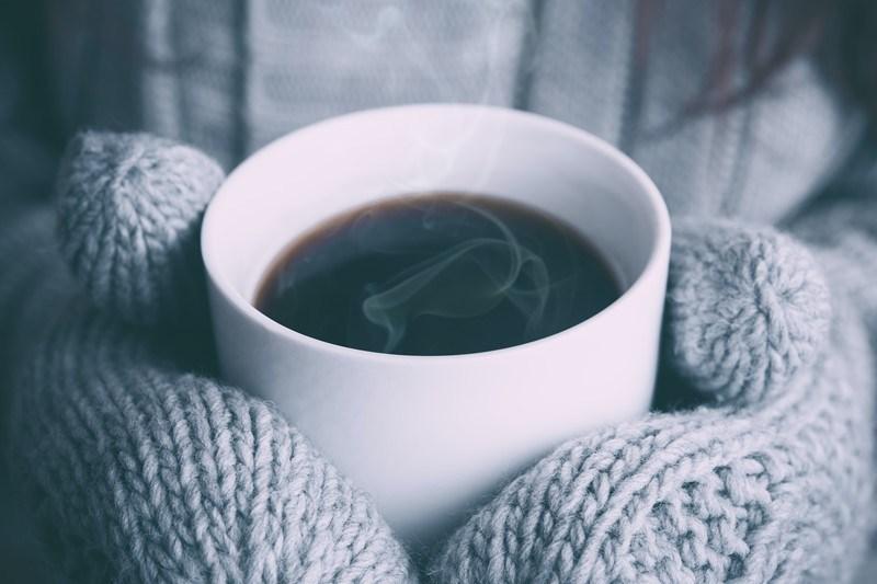 Person hält Kaffeetasse in warmen Handschuhen