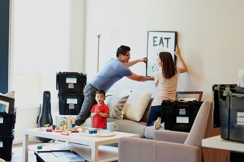 Eine Familie richtet eine neue Wohnung ein und hängt ein Bild auf.