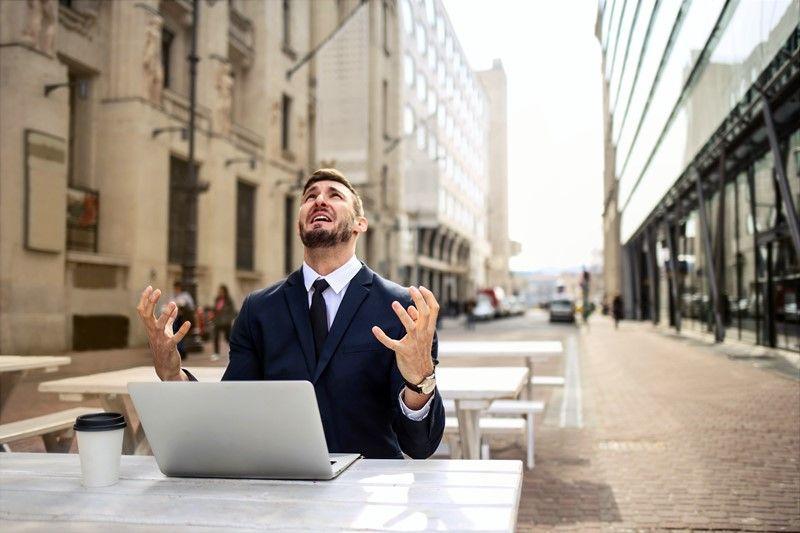 Frustrierter Mann vor einem Laptop in einem Straßencafé