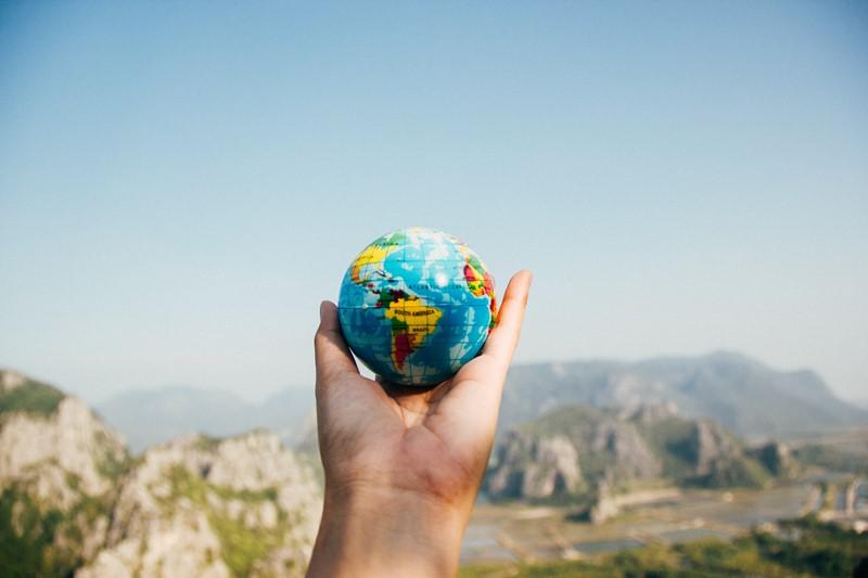 Urlaub in Ferienwohnung - Mann hält kleinen Globus in Hand vor Landschaft