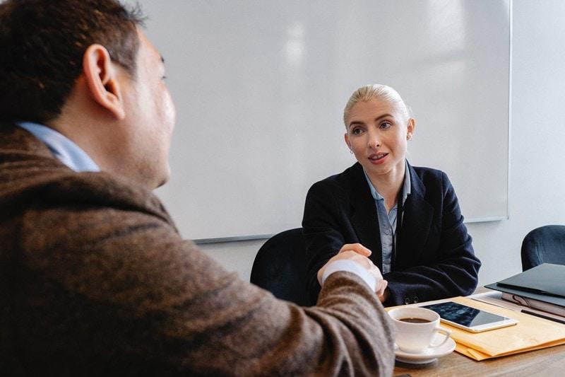 Frau schüttelt Mann bei einem Business Meeting die Hand.