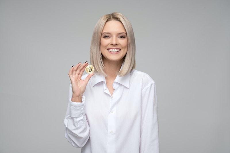 Frau hält Bitcoin-Münze hoch