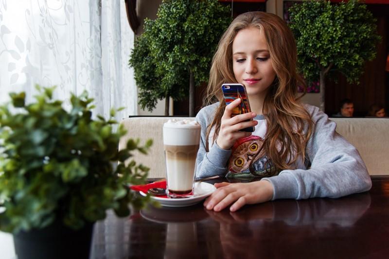 Eine junge Frau nutzt ihr Smartphone im Café
