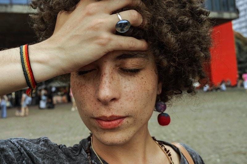 Junge Frau ist verzweifelt und fasst sich an den Kopf.