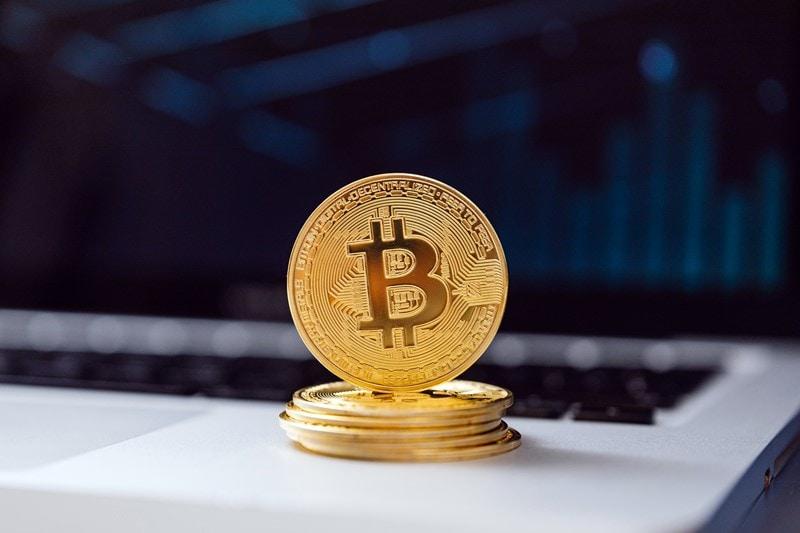 Bitcoin Münzen liegen auf einem Notebook