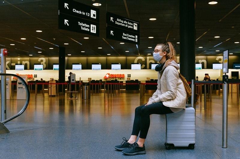 Frau mit Maske und Koffer am Flughafen