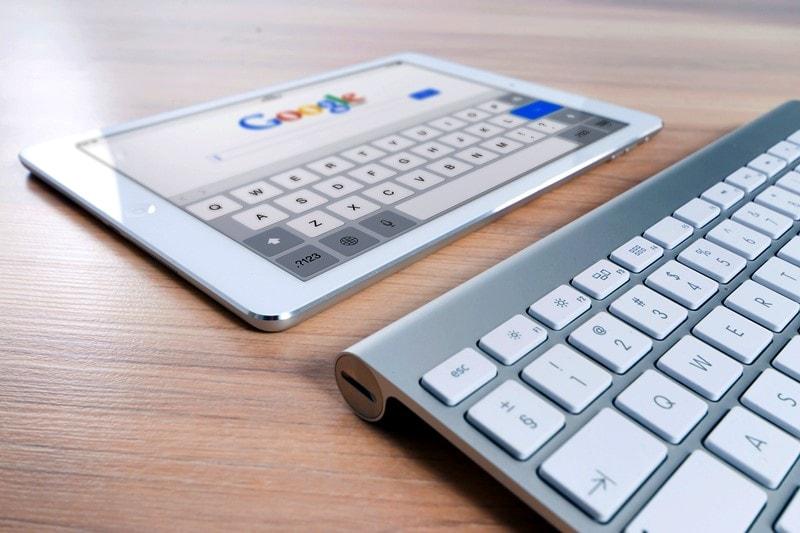 Eine Tastatur liegt vor einem Tablet mit der geöffneten Google Website.