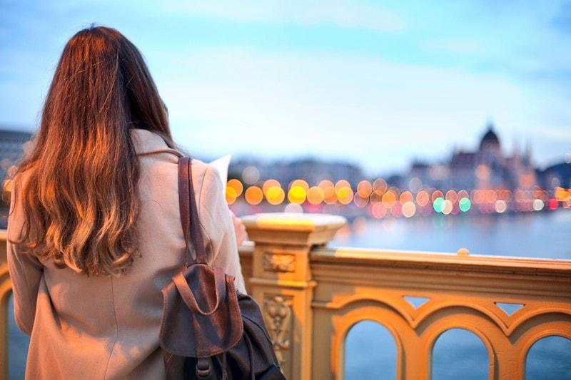 Frau blickt abends auf die Donau in Budapest