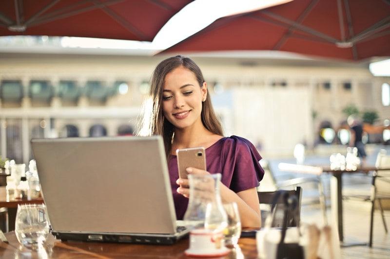 Frau nutzt Smartphone und Laptop in einem Außencafé
