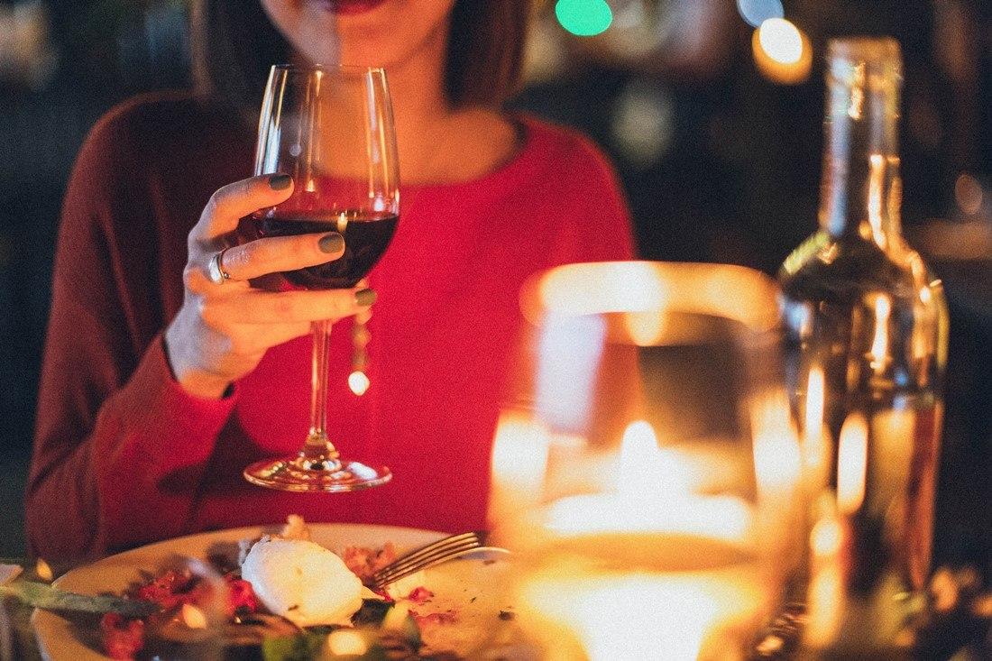 Frau trinkt Wein zum Essen