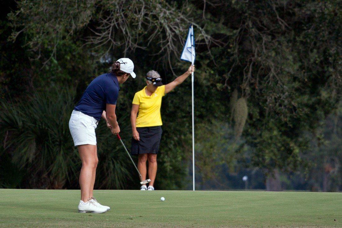 Golferin nutzt Putter, um Ball in Loch zu versenken.