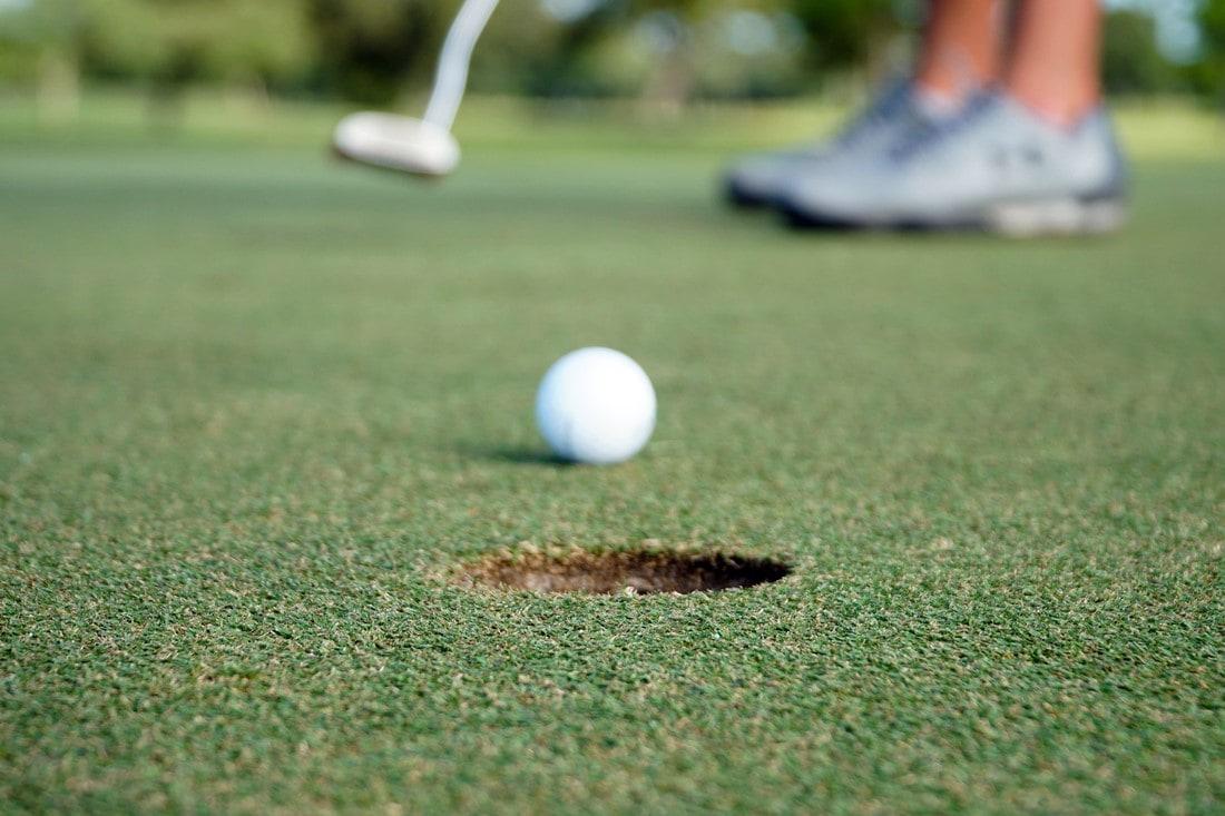 Golfspielerin spielt Golfball in Richtung Loch